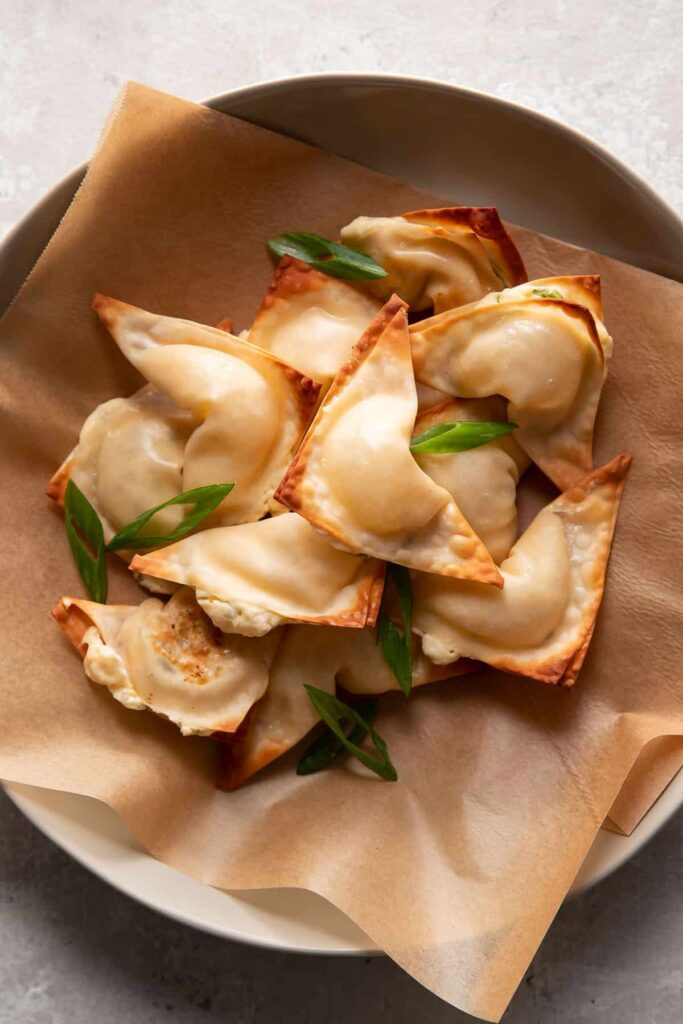 cream cheese wontons in a bowl with green onions on top