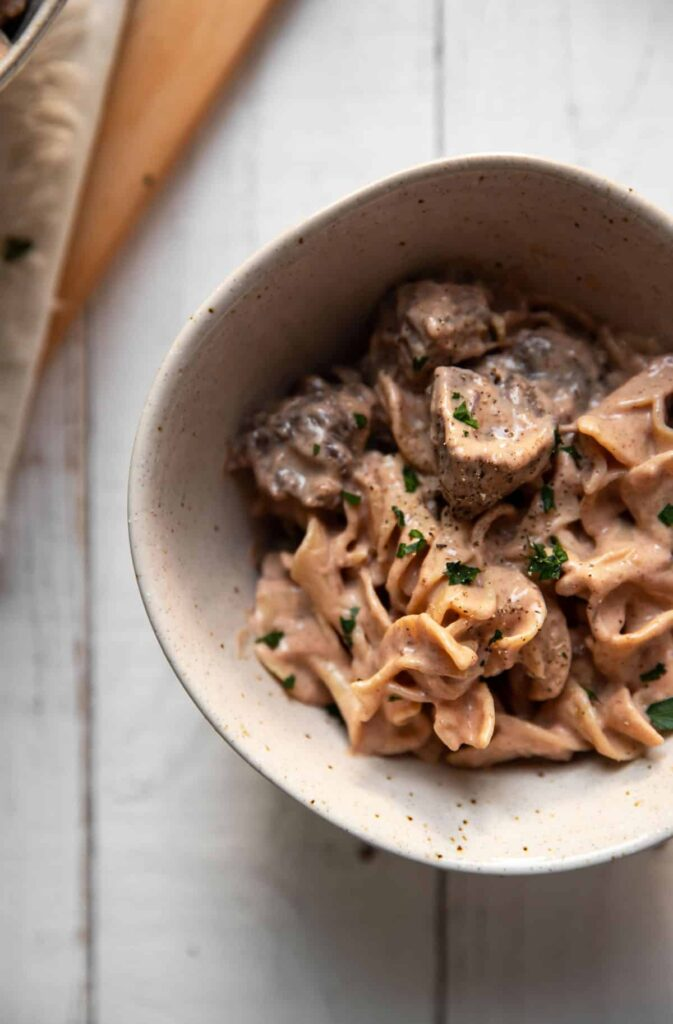 bowls of creamy beef stroganoff with chopped parsley on top