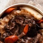 bowl of short ribs braised in the oven with gravy carrots and mashed potatoes