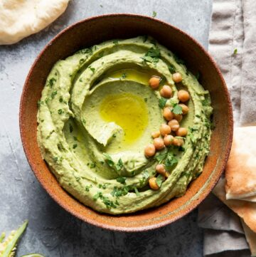 bowl of cilantro jalapeno hummus with olive oil drizzle and chickpea garnish