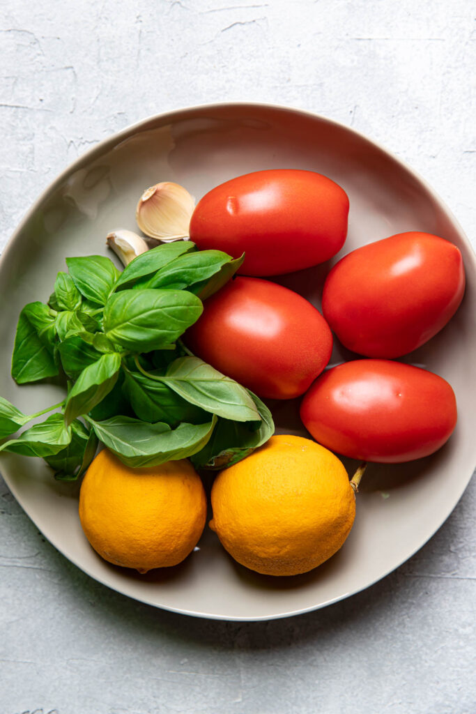 Bowl of tomatoes, lemons, basil and garlic.