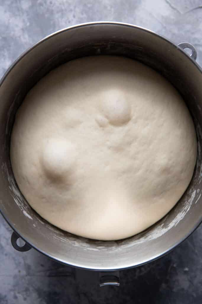 homemade pizza dough in a mixing bowl