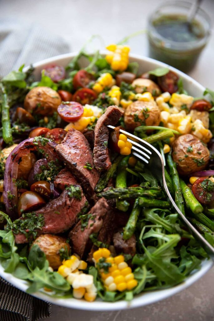 steak salad with chimichurri asparagus corn tomatoes onion in a white bowl