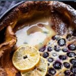 puffy blueberry dutch baby pancake with lemon curd on top and two lemon slices in a cast iron skillet