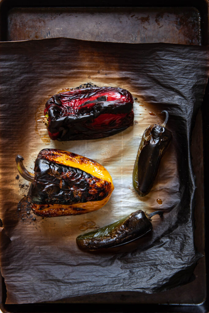 Roasted bell peppers on a baking sheet.