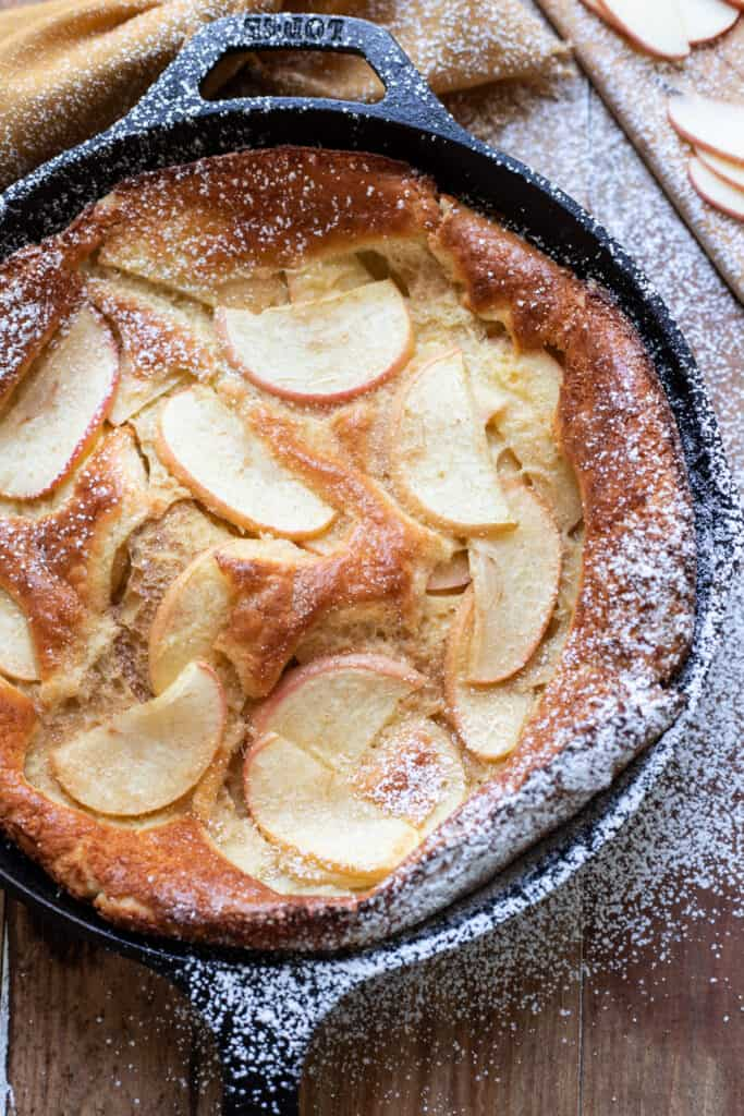 Beautiful, puffy cinnamon apple dutch baby.  Crispy buttery edges and  dreamy honey crisp apples make this cinnamon apple dutch baby pure perfection.  A dust of cinnamon sugar completes it.