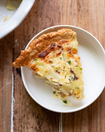 A hearty quiche made up of sliced potatoes, crispy pieces of bacon, green onion and a delicious cheesy sauce.