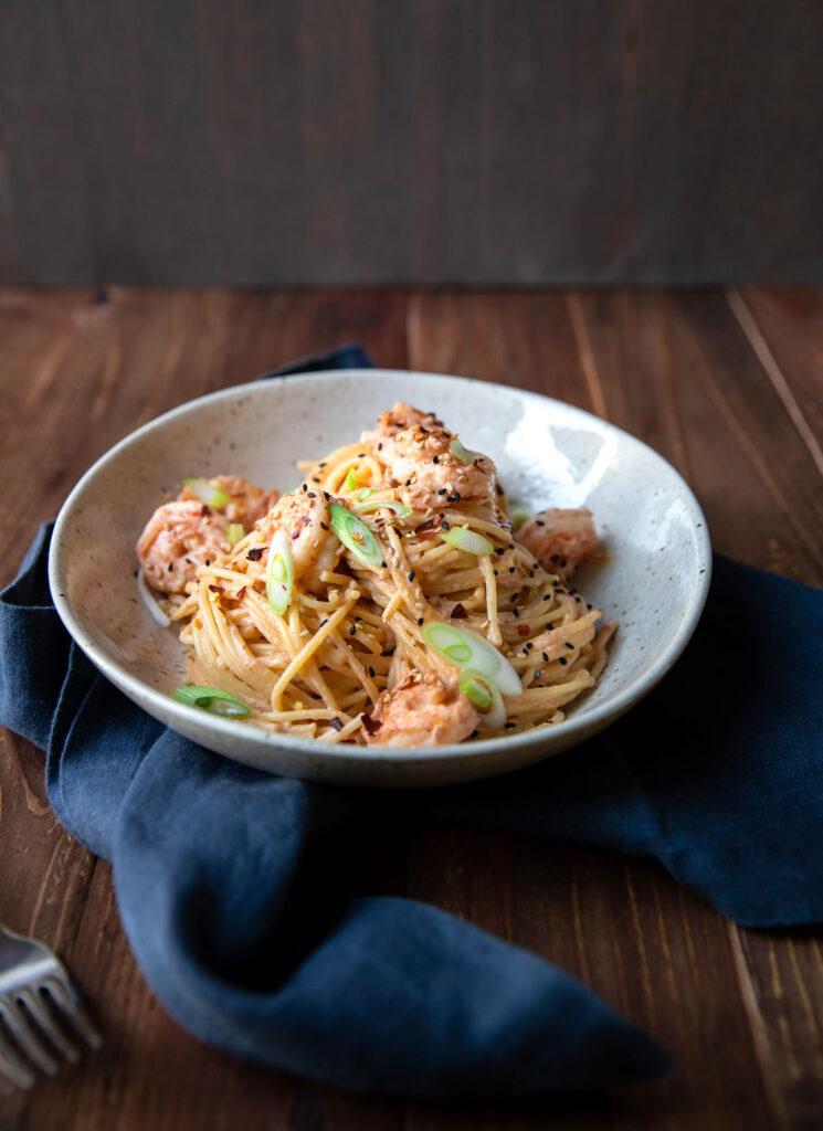 spicy bang bang shrimp pasta and green onions in a bowl
