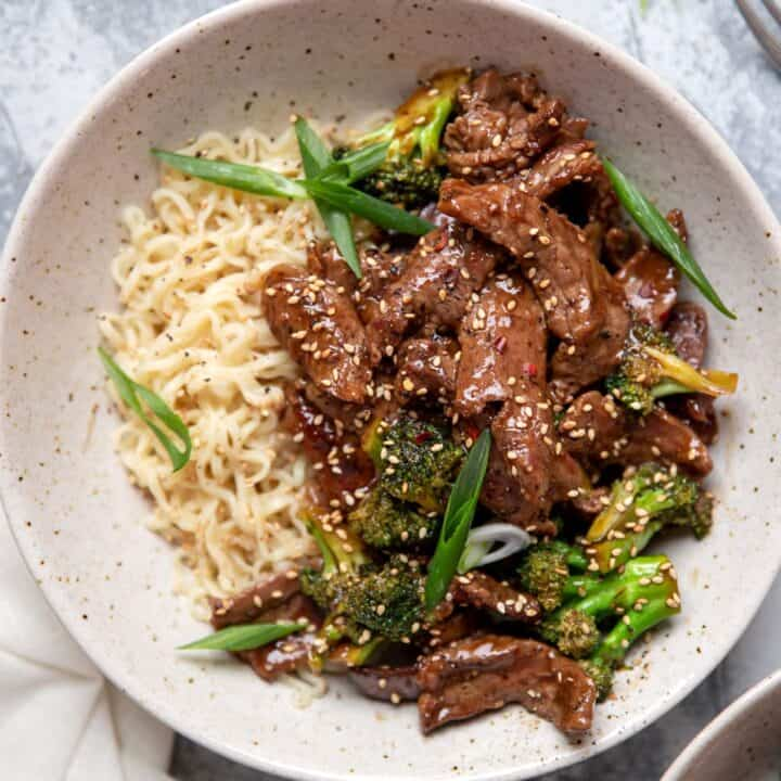 bowl of beef and broccoli with ramen noodles sesame seeds and green onions