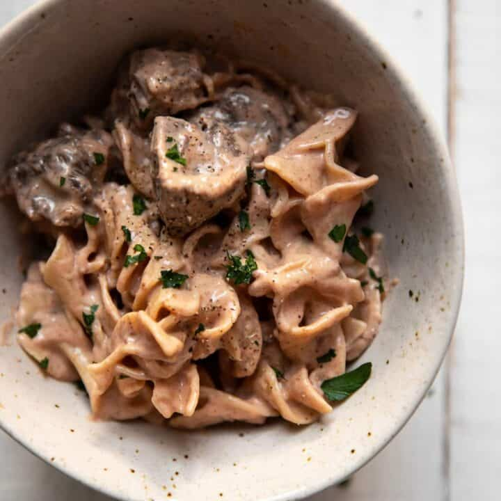 Beef stroganoff and egg noodles in a bowl.
