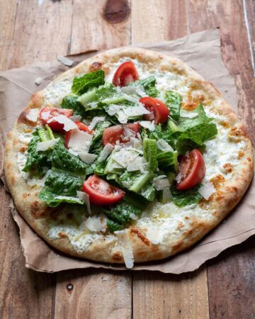 cheese pizza with caesar salad and tomatoes on top
