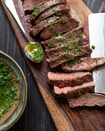flat iron steak with chimichurri sauce on a cutting board