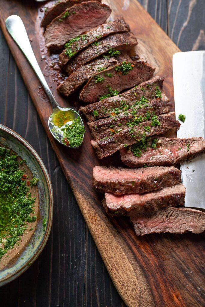 flat iron steak with chimichurri sauce on a cutting board