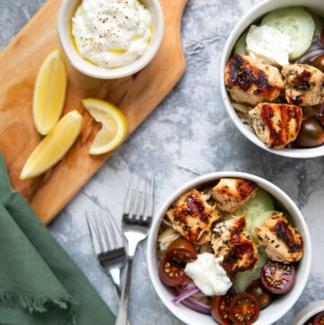 greek chicken cooked on kabobs in a bowl of orzo with tzatziki tomatoes and cucumbers
