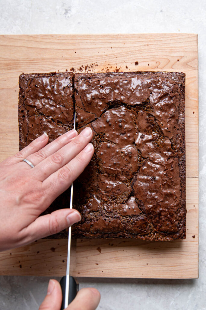 Hand cutting into a batch of brownies.