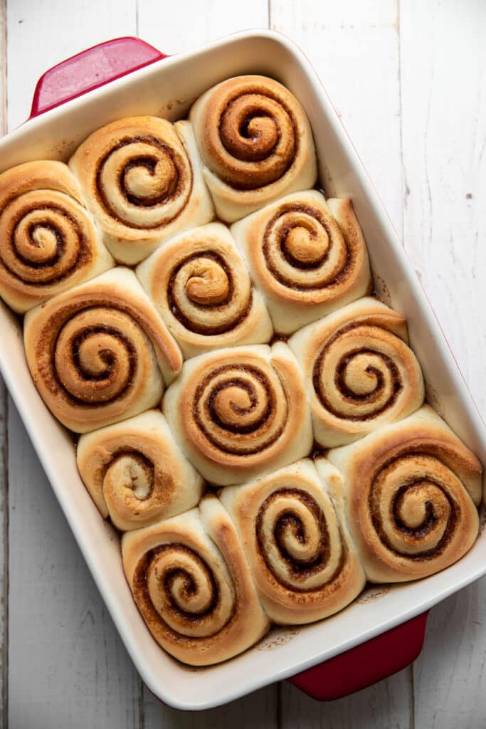 cooked cinnamon rolls in a baking pan