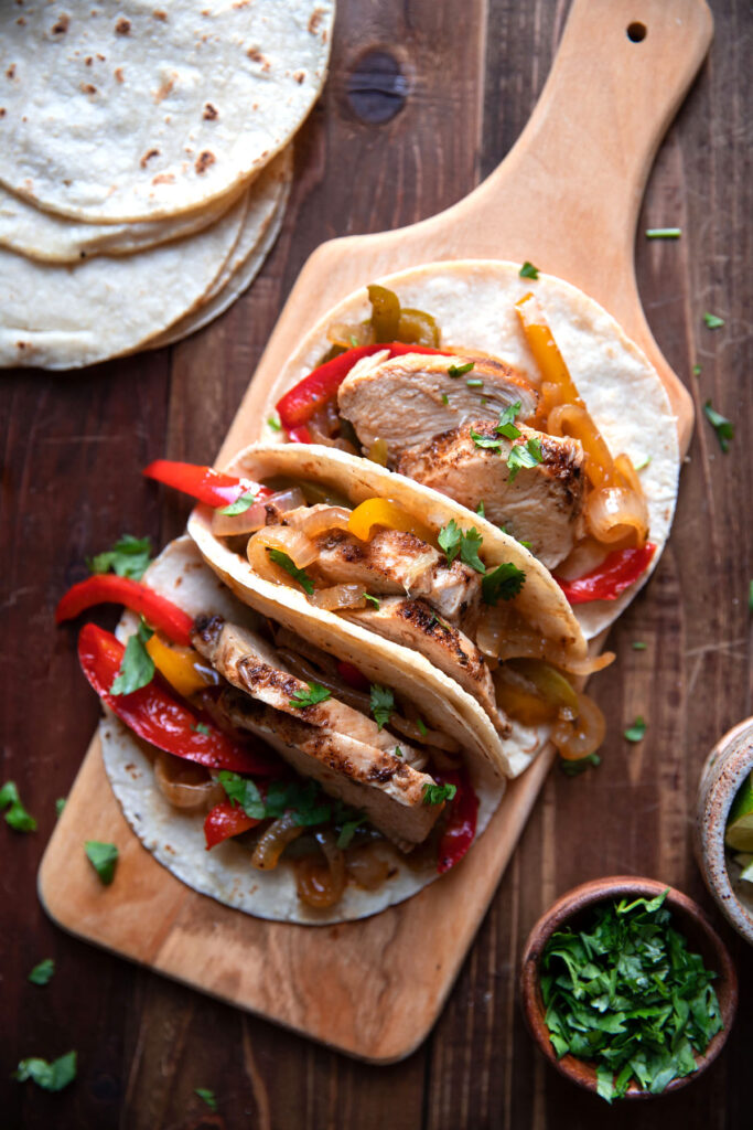 chicken fajitas with bell peppers on a cutting board