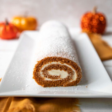 pumpkin roll log with cream cheese frosting and powdered sugar on top
