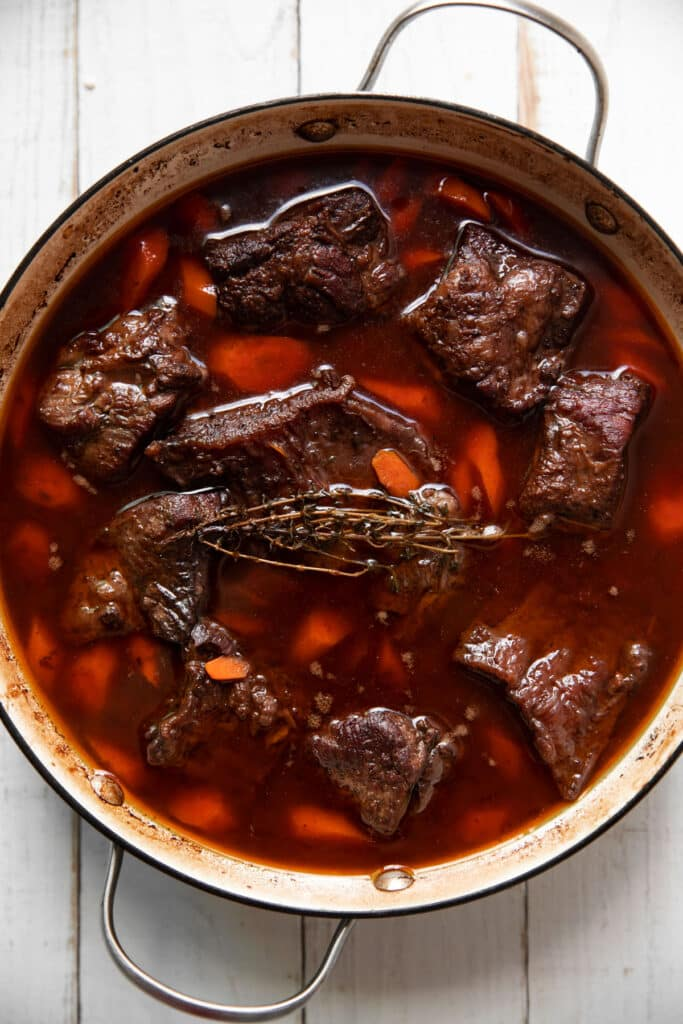 bone in short ribs cooking in a red wine sauce with carrots
