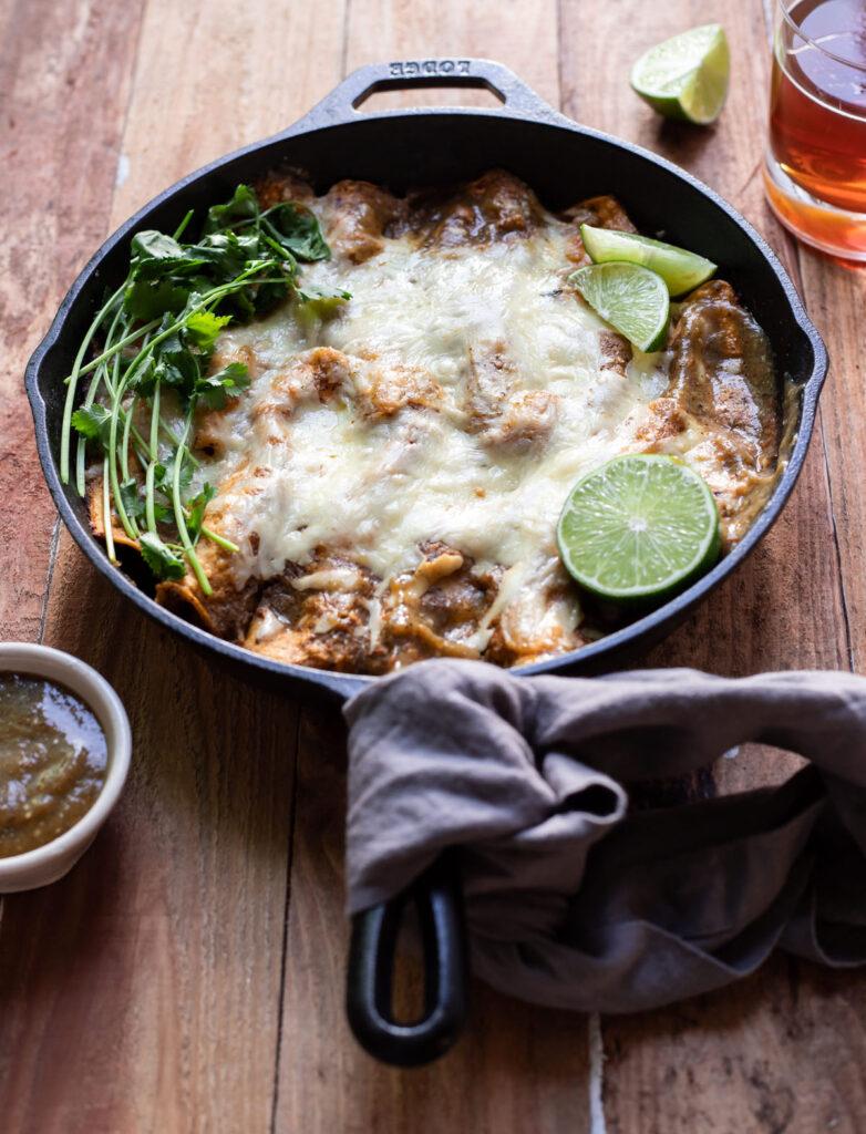 corn tortilla short rib enchiladas in a skillet