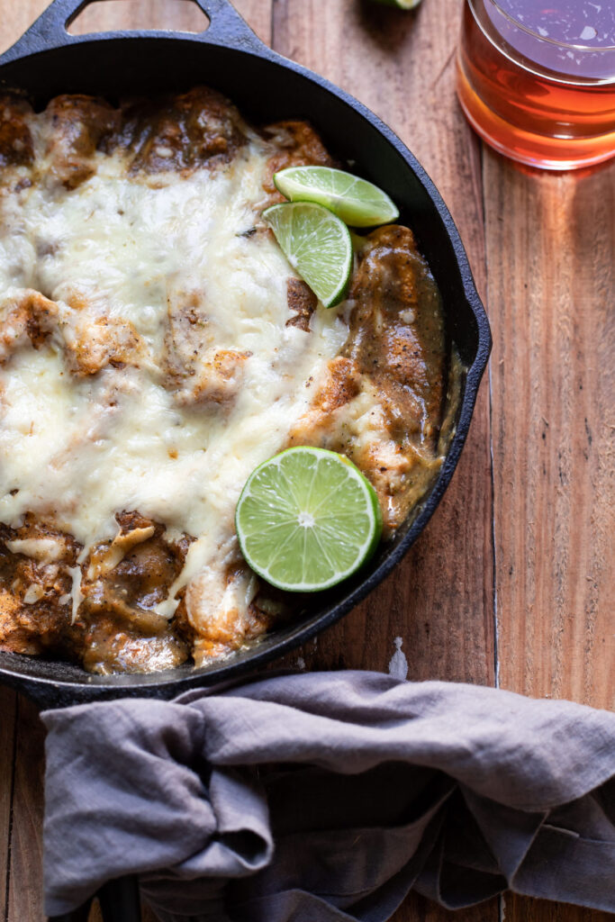 corn tortilla short rib enchiladas in a skillet