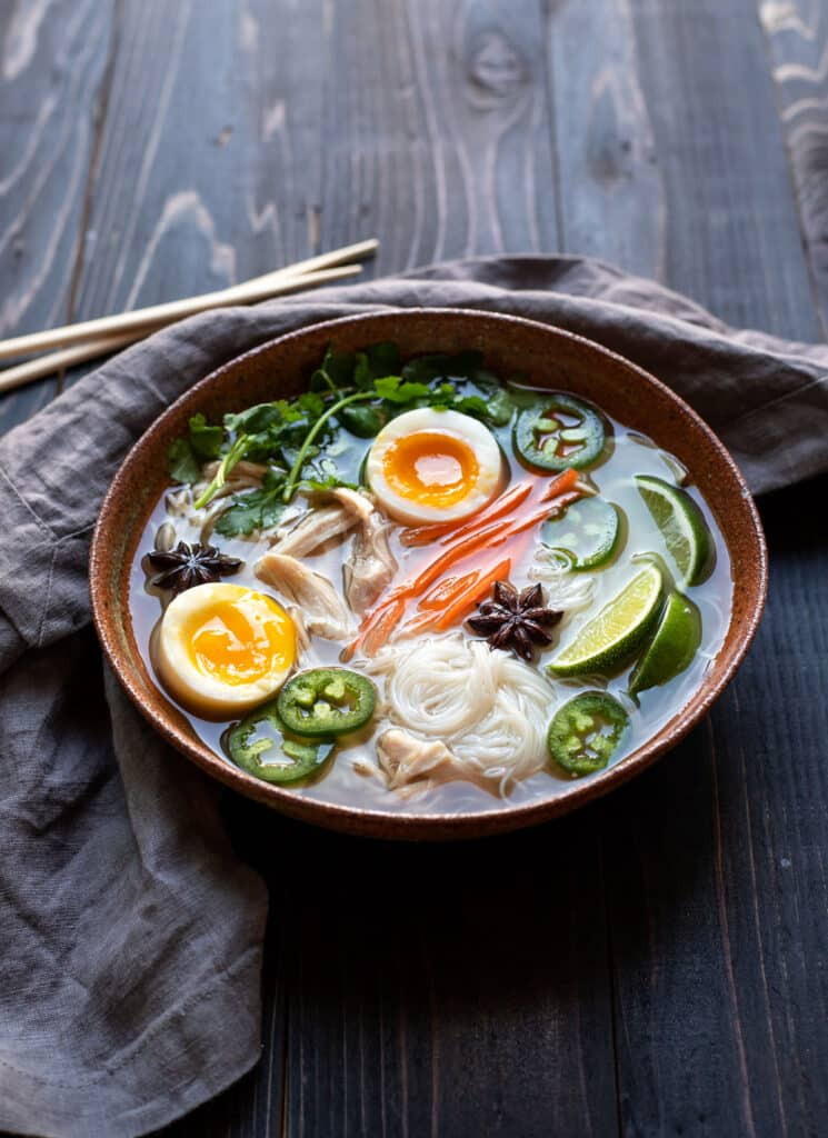 bowl of chicken pho with soft boiled egg jalapeno cilantro rice noodles