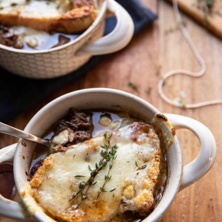 bowl of pot roast and french onion soup with swiss cheese melted over bread