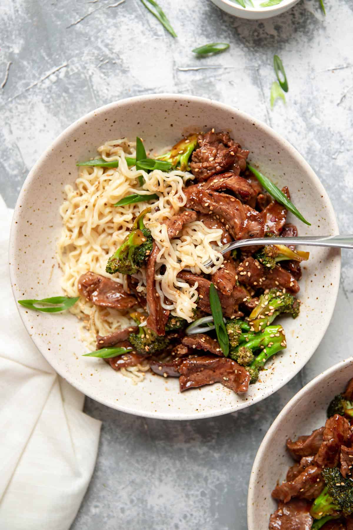 beef and broccoli with ramen noodles in a bowl.