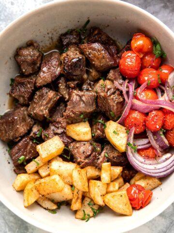 slow cooker steak bites with butter lemon sauce tomato and crispy potatoes