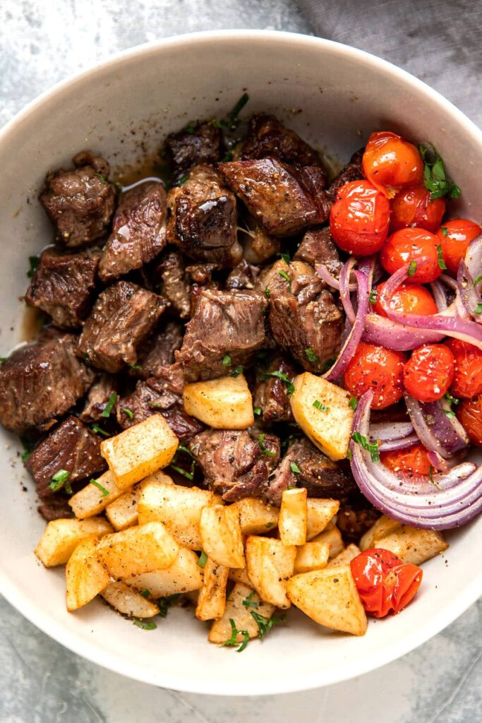 slow cooker steak bites with butter lemon sauce tomato and crispy potatoes