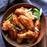 chicken wings tossed in an asian zing sauce with green onions and lime wedges in a bowl