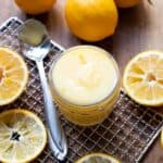 lemon curd in a jar with lemon slices around it