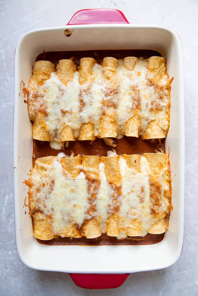 enchiladas with cheese on top in a pan after cooking
