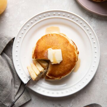 buttermilk pancakes on a plate with butter and maple syrup on top