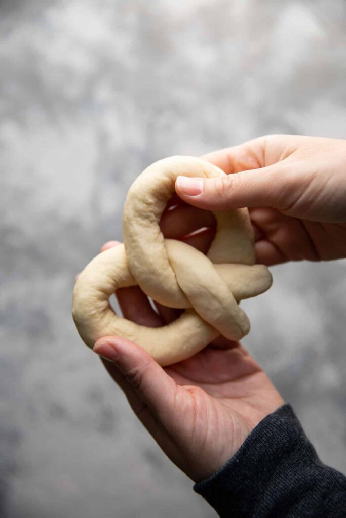 hand holding an uncooked soft pretzel
