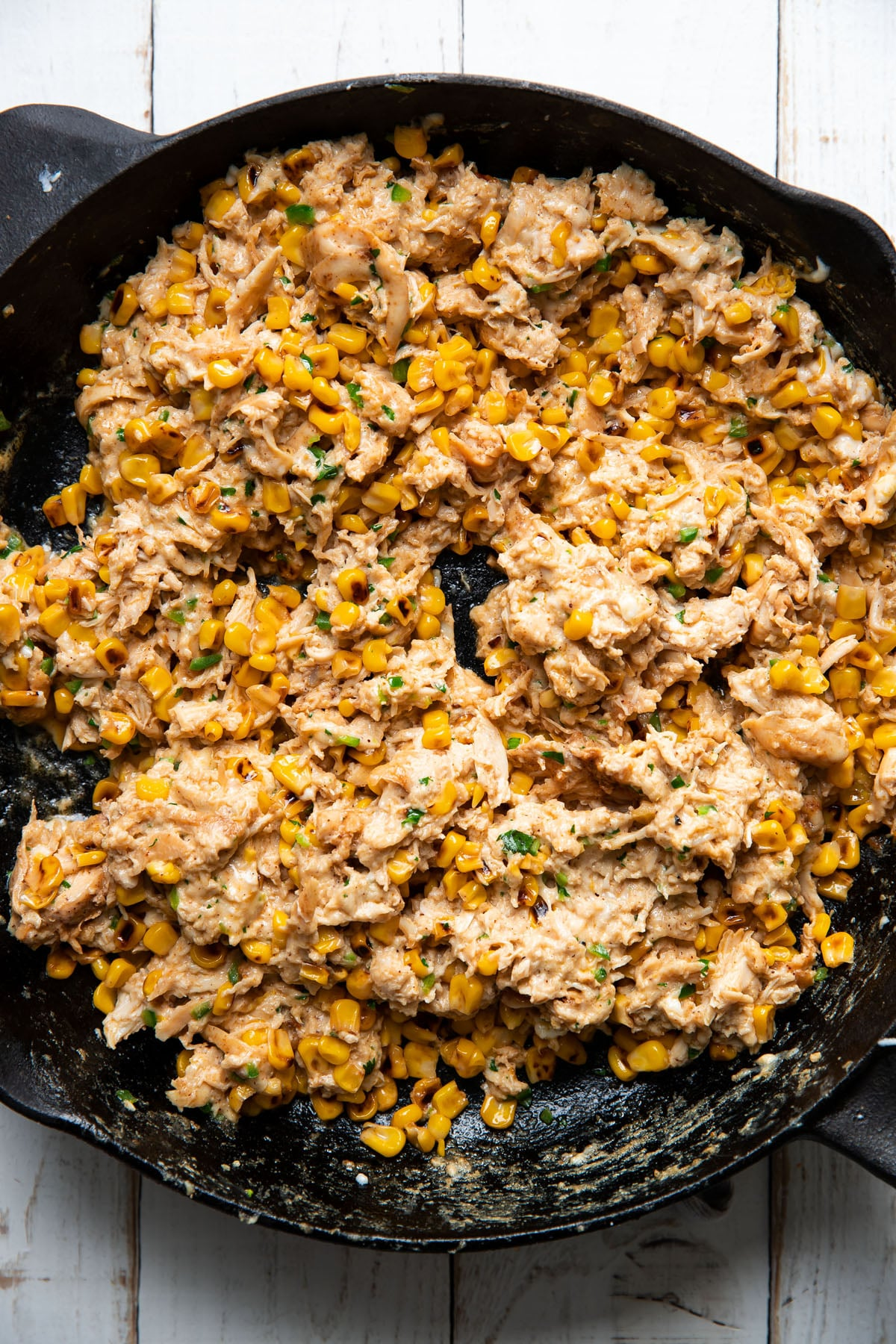 shredded chicken and mexican street corn mixed together in a skillet