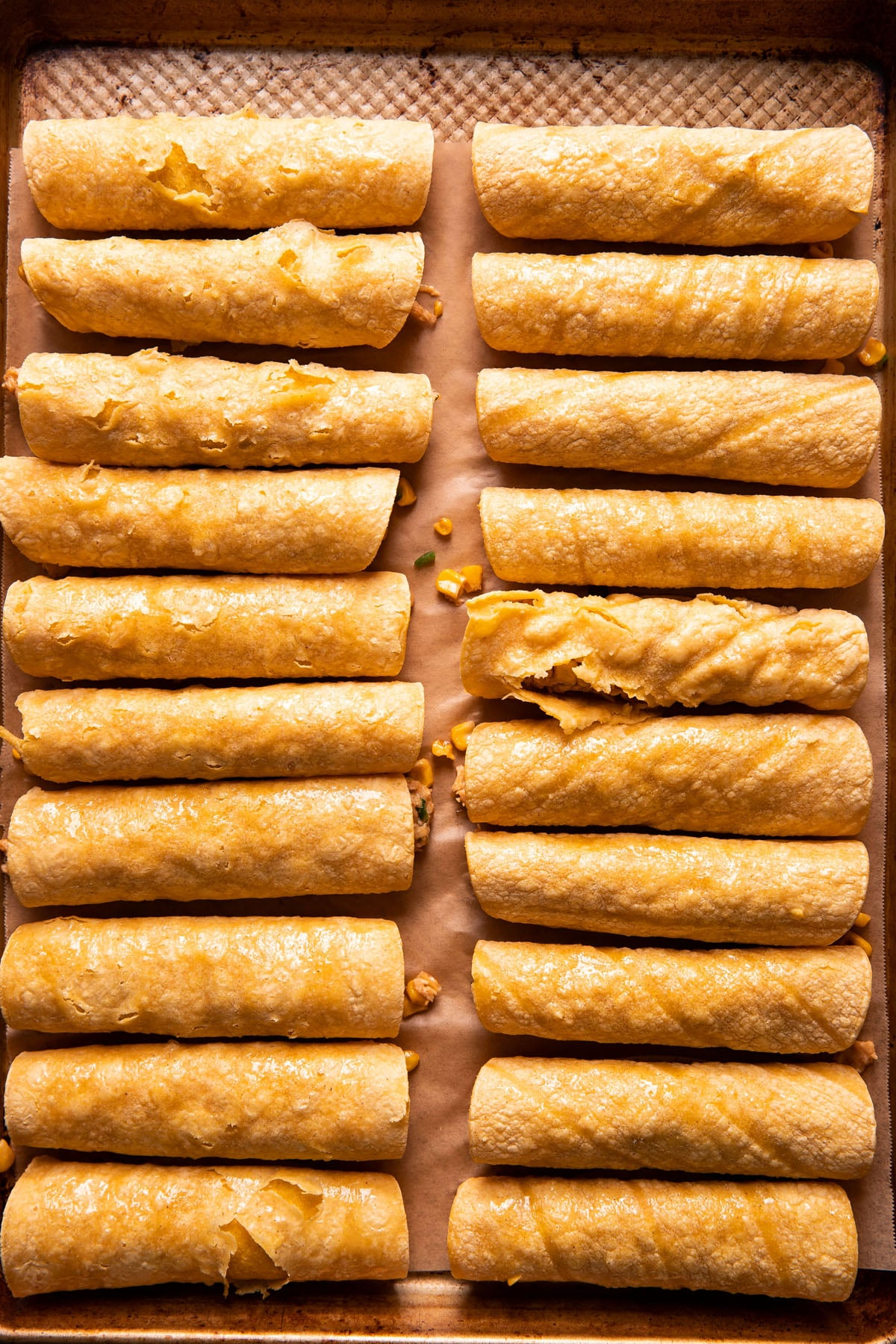 two rows of taquitos on a baking sheet before being baked