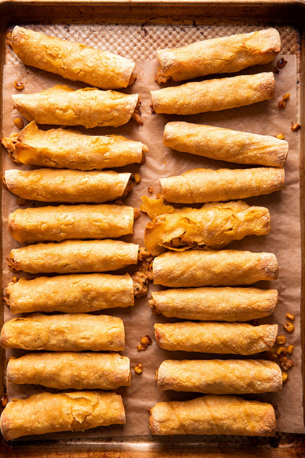two rows of taquitos on a baking sheet after being baked