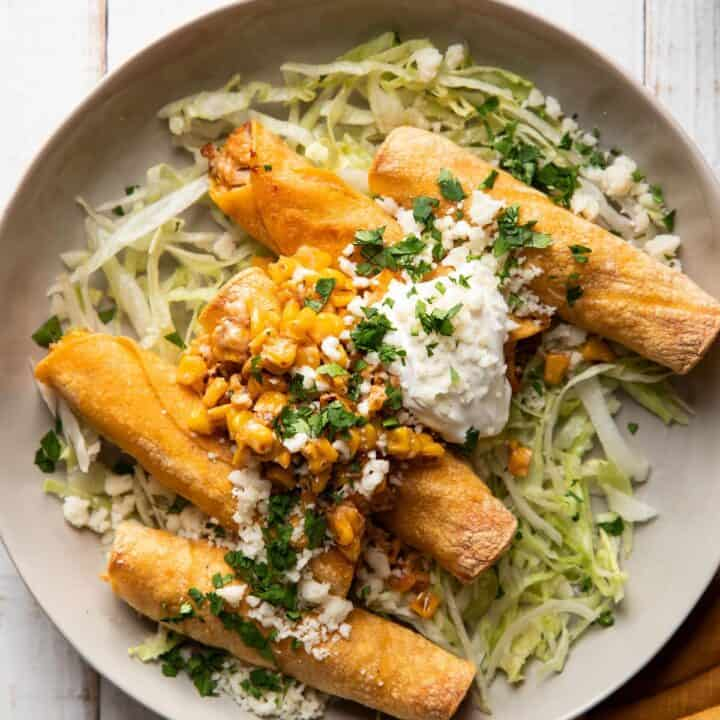 plate of taquitos filled with chicken and mexican corn served with lettuce and sour cream on top