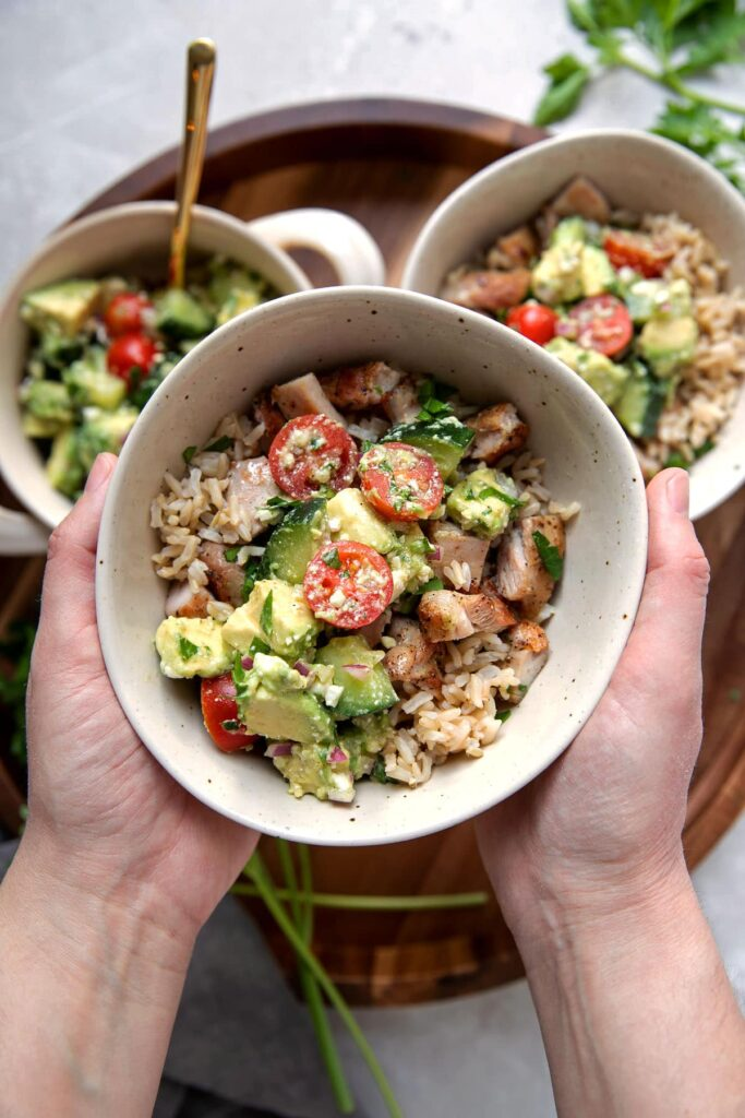 hands holding a bowl of greek marinated chicken thighs with brown rice and avocado feta dip