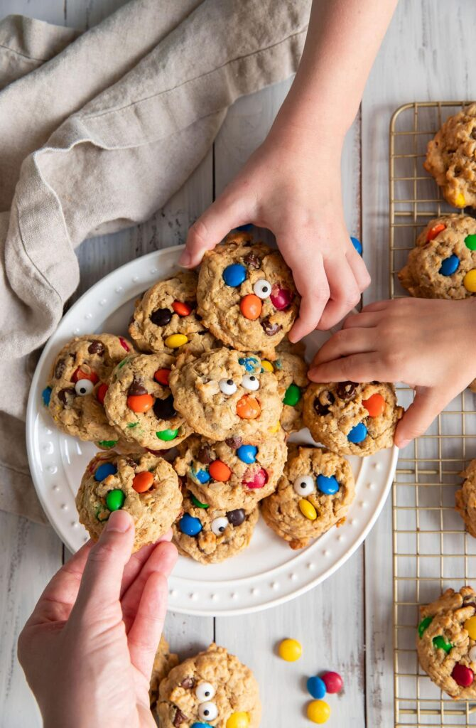 3 hands reaching for monster cookies on a plate