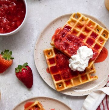 belgian waffles with strawberries and whipped cream on a plate