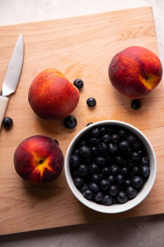 peaches and blueberries on a cutting board