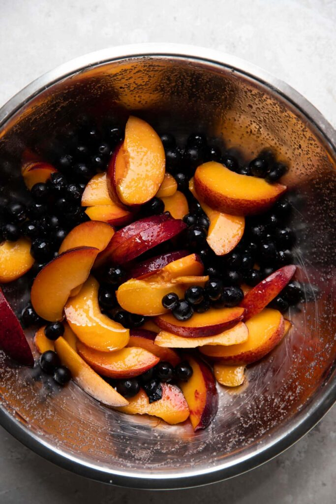 bowl of blueberries and peaches tossed with sugar and honey