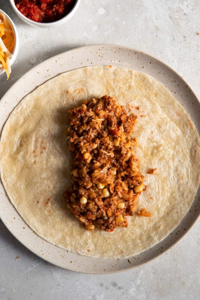 mexican beef and rice on a tortilla on a plate