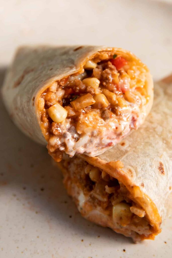 mexican beef and rice rolled up in to a burrito with sour cream inside