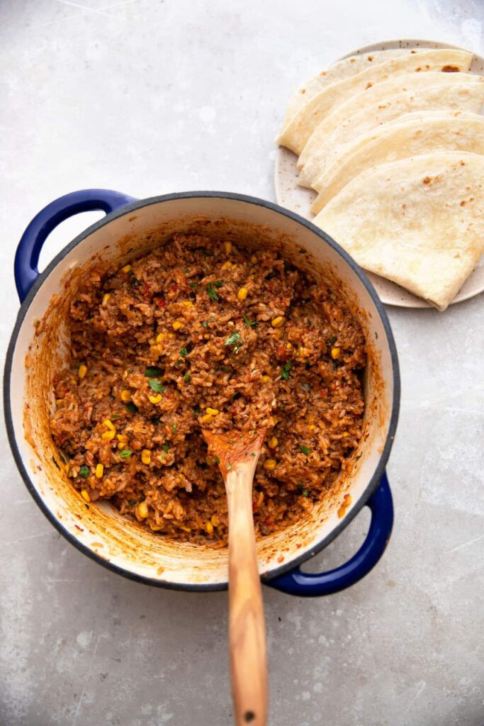 mexican beef and rice in a cast iron pot with tortillas on the side