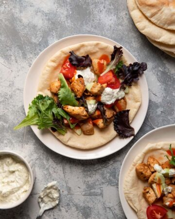 chicken pitas on a plate with tomato lettuce and tzatziki sauce