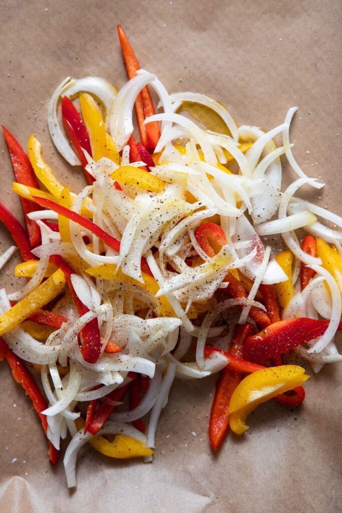 sliced bell peppers and onions on a sheet pan