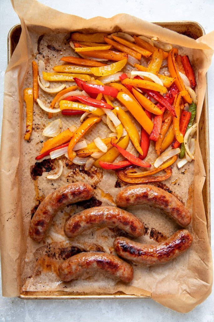 cooked italian sausages peppers and onions on a sheet pan